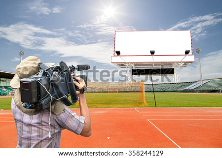 Professional cameraman and Video camera operator working with Empty white digital billboard screen for advertising in stadium and Running Trace, soccer field grass Goal at the stadium Soccer field - stock photo