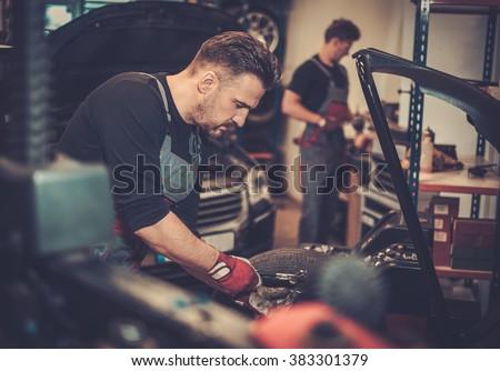 Professional car  mechanic balancing car wheel on balancer in auto repair service. - stock photo