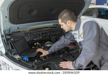 professional car mechanic working in auto repair service with laptop