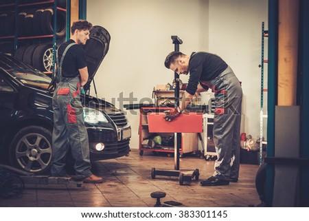 Professional car mechanics inspecting headlight lamp of automobile in auto repair service. - stock photo