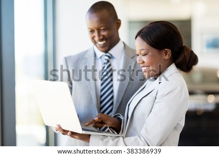 professional car sales consultants working on laptop computer inside vehicle showroom - stock photo