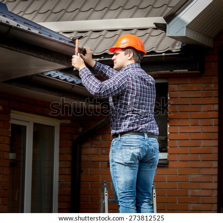 Professional carpenter hammering roof boards with hammer - stock photo