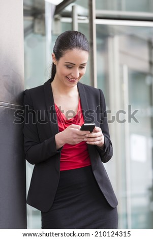 Professional Caucasian businesswoman outside in modern city using a Cell Phone. Cheerful woman talking on smartphone. - stock photo
