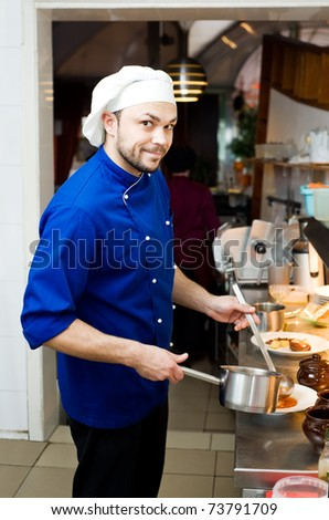 professional chef cooking in commercial kitchen with scoop - stock photo
