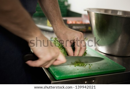 Professional chef cutting herbs for garnish - stock photo