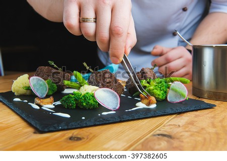 Professional chef decorate plate with meat greens. Young chef prepares delicious meals in  restaurant kitchen. Chunks of roasted meat on a black plate with greens, cherry tomatoes and sauce. Close-up. - stock photo