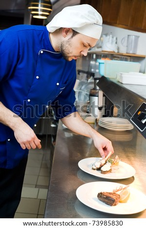 professional chef decorating prepared food on plates in commercial kitchen - stock photo