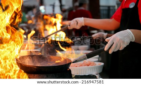 Professional Chef in a Commercial Kitchen Cooking Flambe. Two chefs cooking in outdoor kitchen. Chef frying food in flaming pan on gas hob in commercial kitchen.  - stock photo