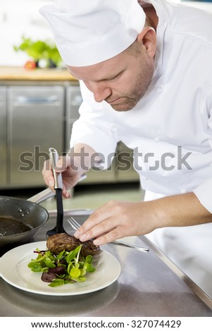 Professional chef prepare meat dish at restaurant - stock photo