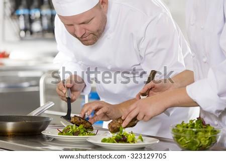 Professional chef prepare steak dish at restaurant - stock photo