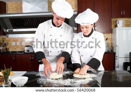 professional chefs hands kneading bread dough on a cutting board - stock photo