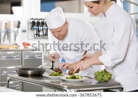 Professional chefs prepare steak dish at restaurant - stock photo