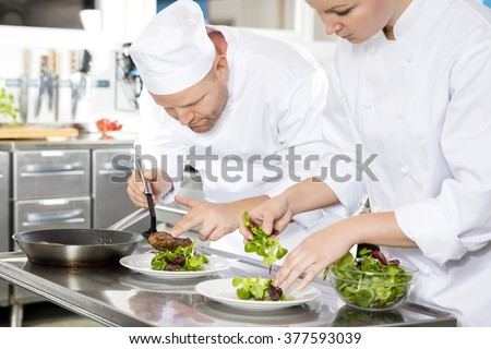 Professional chefs prepares beef meat dish in a professional kitchen at gourmet restaurant or hotel. - stock photo