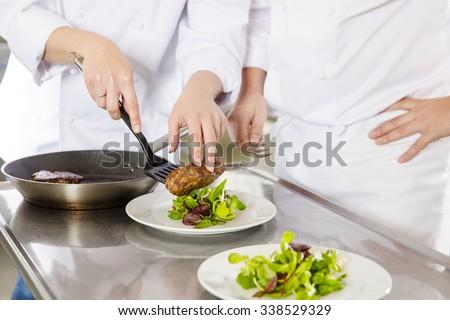 Professional chefs prepares steak dishes at restaurant - stock photo