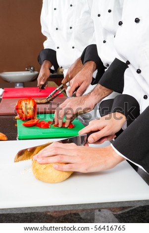 professional chefs preparing food in commercial kitchen - stock photo