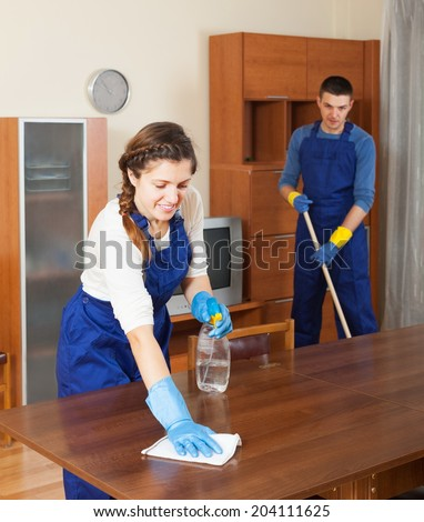 Professional cleaners dusting wooden furiture at living room - stock photo