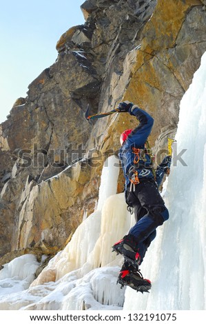 Professional climber on icy waterfall - stock photo