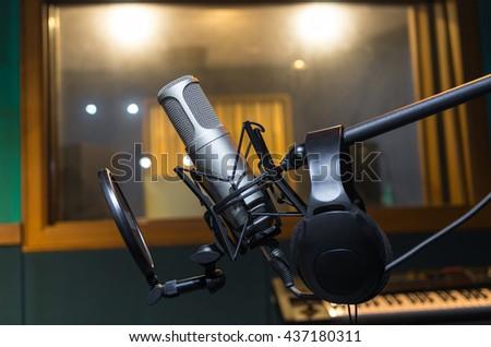 Professional condenser studio microphone with Earphone in dark studio background, Musical Concept - stock photo