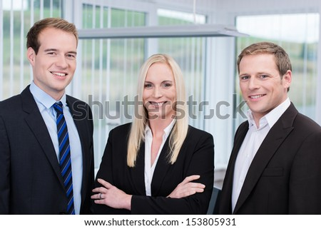 Professional confident young happy team made of two handsome men and a blond long haired woman between them, all smiling and wearing business clothes, in the office - stock photo