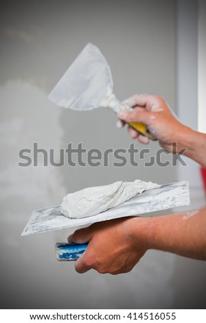 Professional construction worker applying skim coating material to the freshly made plasterboard wall before painting.