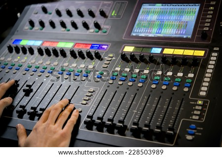 Professional control panel with operator hands in the recording studio