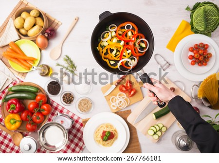 Professional cook frying fresh sliced vegetables in a nonstick pan hands close up, food ingredients and kitchenware on background, top view - stock photo