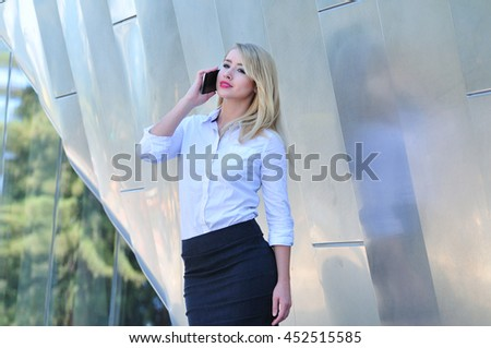 Professional corporate woman in business attire talking on mobile phone in the city - stock photo