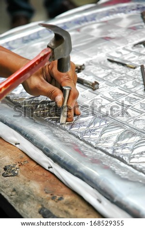 Professional craftsman working in a metal carving - stock photo