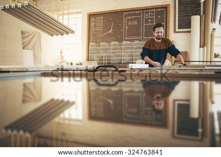Professional craftsman working with skill and concentration in his naturally lit studio - stock photo