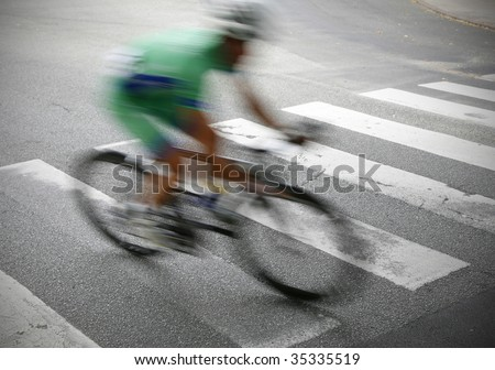 Professional cyclist rushing by just before the finishing line in a great Danish race. - stock photo