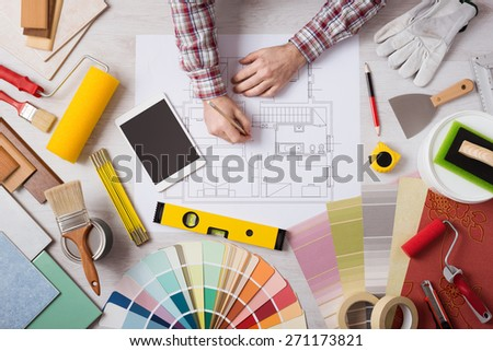Professional decorator drawing on a house project with work tools, painting rollers and color swatches all around, top view - stock photo