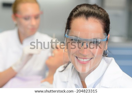 Professional dentist with protective glasses patient woman dental checkup - stock photo