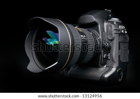 Professional digital photo camera with zoom lens on black background - stock photo