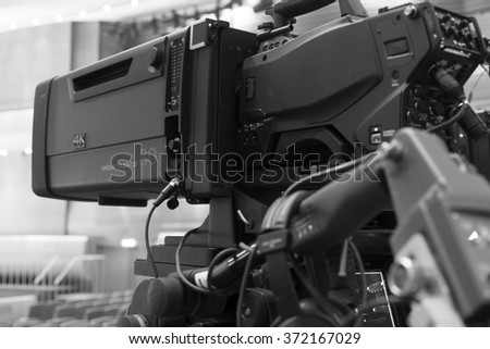 Professional digital video camera. accessories for 4k video cameras. tv camera in a concert hall.  black and white photo - stock photo
