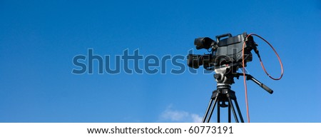 Professional digital video camera on tripod, on blue sky background - stock photo