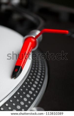 Professional DJ audio equipment - shperical turntable needle on white vinyl record - stock photo