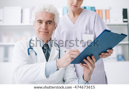 Professional doctor and his assistant working in the office, she is holding a clipboard and he is signing medical records