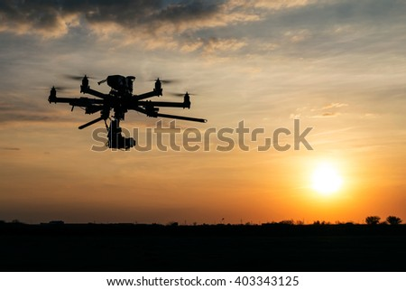 Professional drone flying in the sunset - stock photo