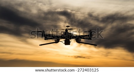 Professional drone flying in the sunset with dark clouds - stock photo