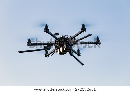 Professional drone hexacopter flying on blue sky - stock photo