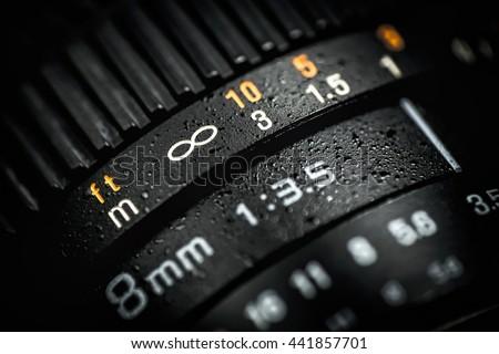 Professional DSLR lens on dark background. Macro photo. - stock photo