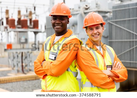 professional electrical engineers with arms crossed in power plant - stock photo