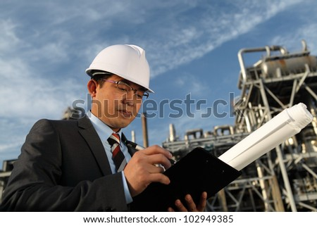 Professional engineer oil gas industry write on note board with large oil industry in the background and blue sky - stock photo