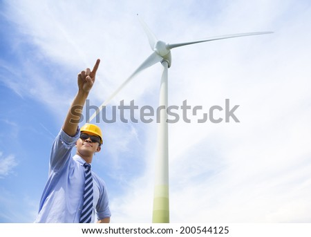 professional engineer raise his finger with wind generator - stock photo