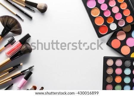Professional equipment of beauty salons for applying flawless make-up. Palettes with blushers, lipstick and eyeshadows in the right corner and brushes with pencils in the left one. Place for text. - stock photo