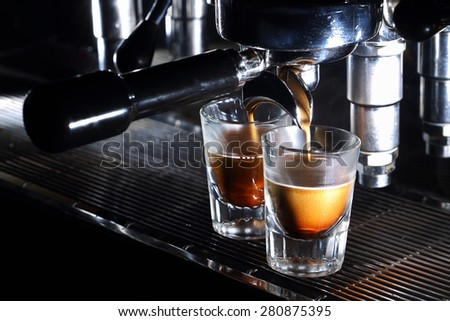 Professional espresso machine brewing a coffee. Coffee pouring into shot glasses. Toned image - stock photo