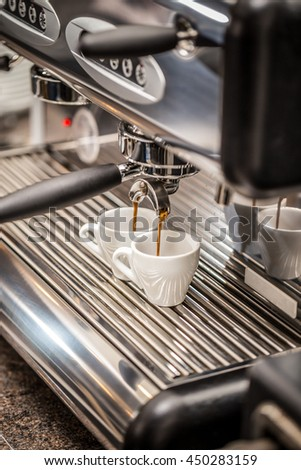 Professional espresso machine pouring strong looking fresh coffee into a ceramic cup
