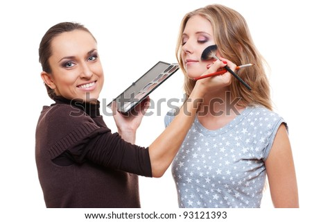 professional esthetician applying eyeshadow from color palette. isolated on white background - stock photo