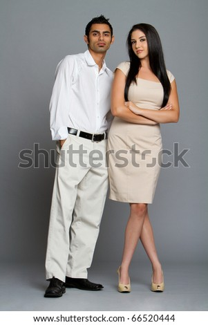 Professional ethnic couple in business clothes - stock photo