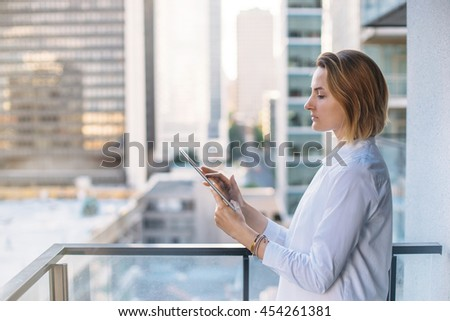 Professional female architect working on new project of office buildings, Tablet on city background, Flare light, Shallow DOF.